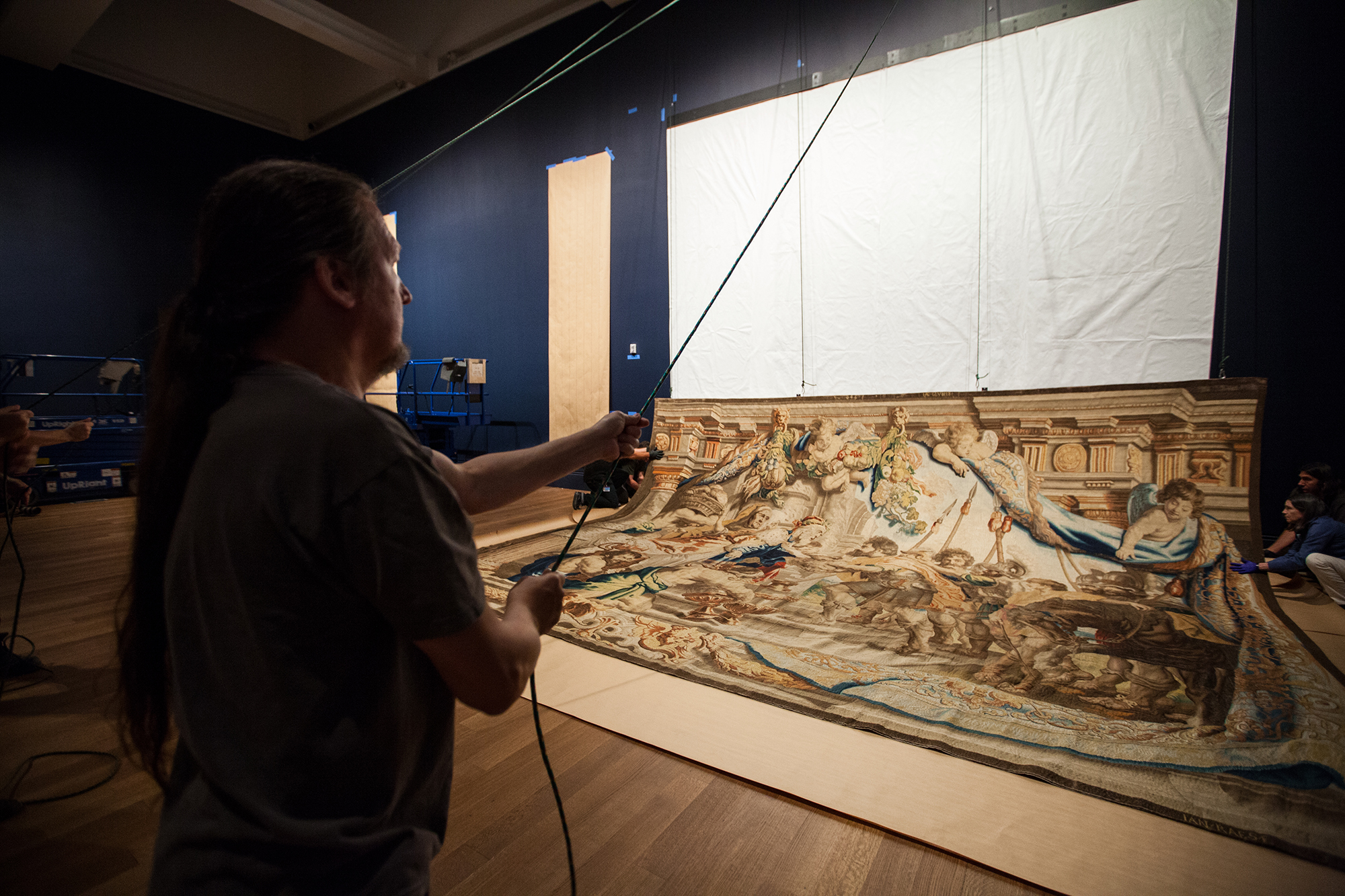 The backside of the tapestry is equipped with Velcro and hooks attached to the tapestry backing used to hoist it up to meet the wall-mounted Velcro.