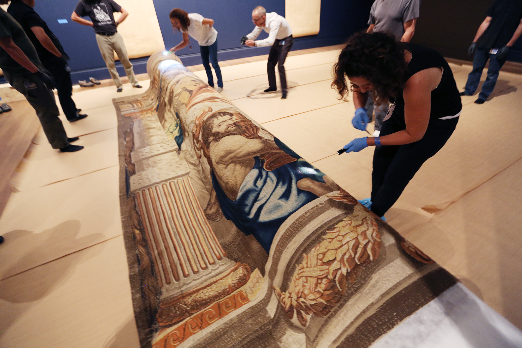 The tapestry is slowly unrolled while conservators check for (and remove) hairs and foreign threads.