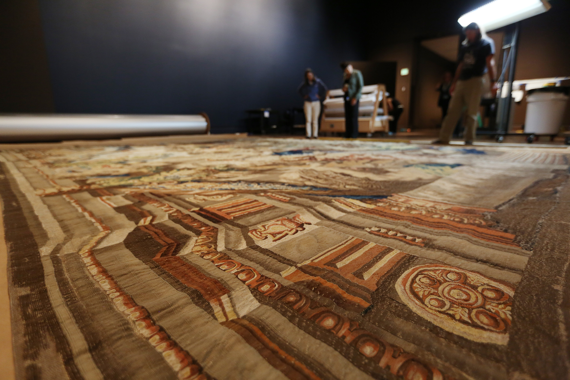 Once unrolled, the tapestry is carefully measured and re-measured in preparation for hanging.
