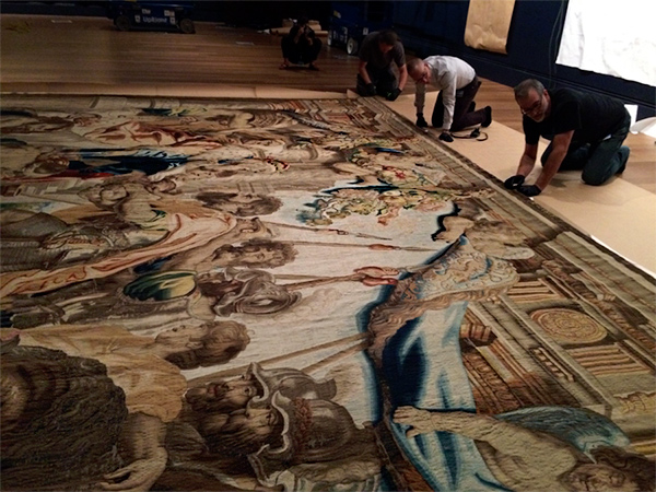 Preparators tap Velcro into place while installing Peter Paul Rubens's tapestries