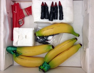 Props used in the Guerrilla Girls' actions: plastic gun, bananas, and gorilla fingers with nail polish