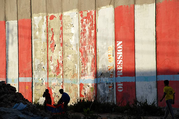 Children in the shadow of the West Bank wall, Bethlehem