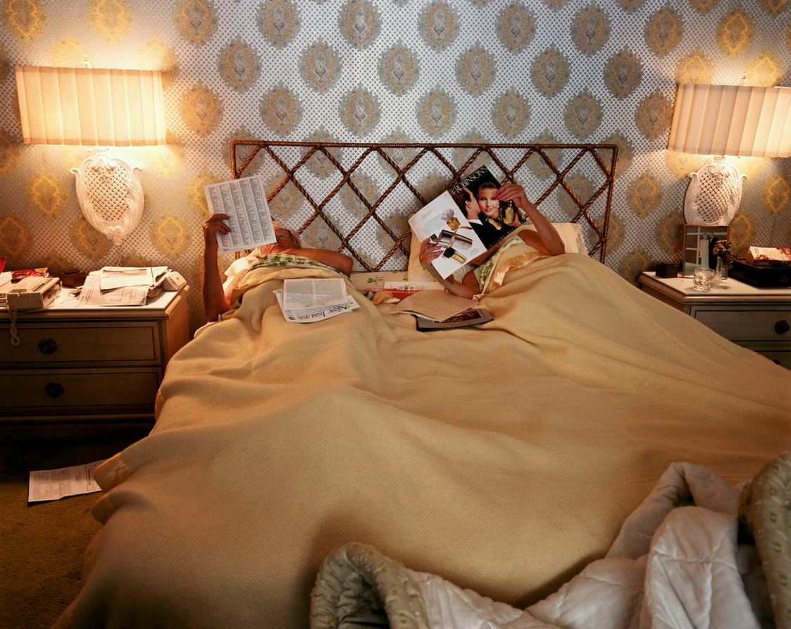 """Reading in Bed from the series """"Pictures from Home"""", 1987, Larry Sultan. Chromogenic print. 20 x 24 inches. Photo courtesy of the Estate of Larry Sultan © Estate of Larry Sultan"""