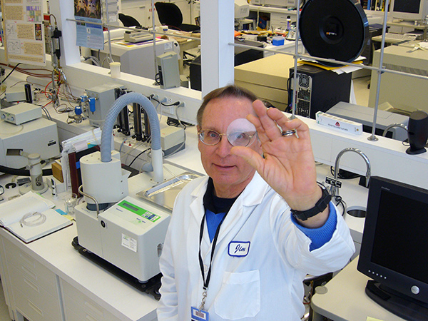 Scientist Jim Druzik holding a clear round lens