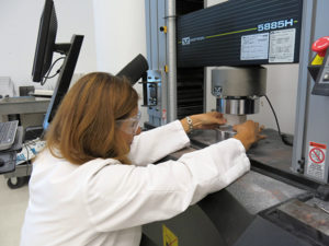 Associate Scientist Beril Bicer-Simsir placing a building material sample in the Universal Testing Machine.