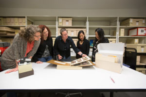 Nancy Enneking, Head of Institutional Records at the Getty, reviews photographs with her team of institutional archivist.