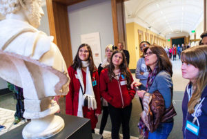 High school students in conversation with docent Barbara Atherton as they examine the Bust of Commodus.