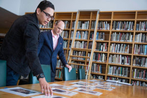 Joseph Valencia and Paul Martineau reviewing copy prints for an exhibition wall