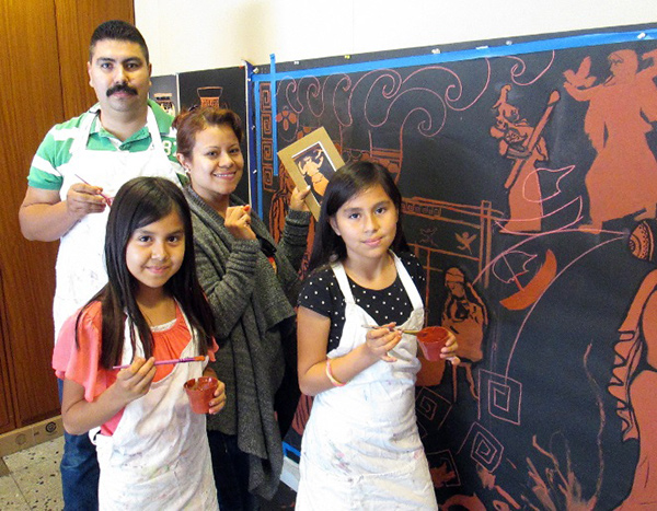 A family works on a mural for a sixth-grade performance of Homer's Odyssey