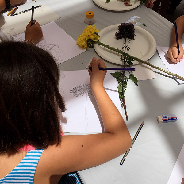 A girl sketches at Family Art Lab: Still Lifes in Blossom