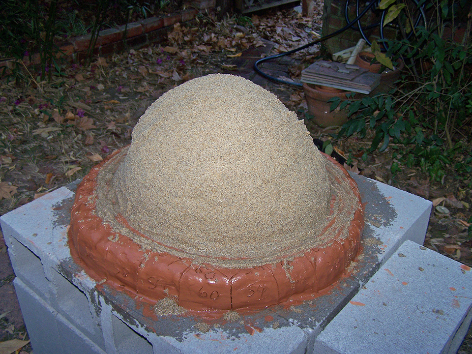 A dome of wet sand atop a homemade bread oven