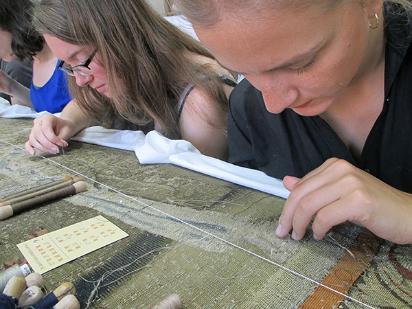 Weavers conserve a tapestry at the Gobelins Manufactory