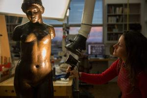 Graduate intern Kellie Boss shines an examination light on Aristide Maillol's Torse de Dina