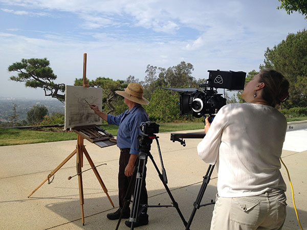 Cinematographer Stacey Rain Strickler captures Timothy as he draws a landscape. Visible on the ground is the shadow of an overhead silk, a film lighting tool.