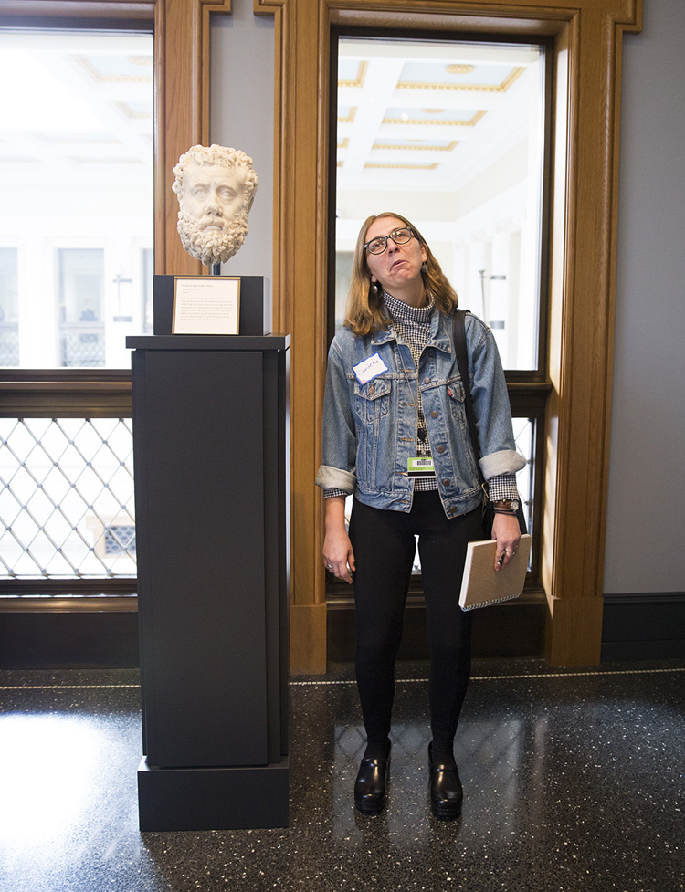 A Getty Villa educator mimics a Roman portrait head