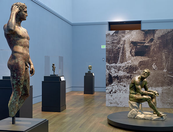 "Gallery view of ""Power and Pathos: Bronze Sculpture of the Hellenistic World."" Foreground, left to right: Victorious Athlete, 300-100 B.C. (The J. Paul Getty Museum) and Seated Boxer, 300-200 B.C. (Museo Nazionale Romano—Palazzo Massimo alle Terme, Rome)."