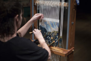 Yadin Larochette at work in the exhibition Woven Gold: Tapestries of Louis XIV