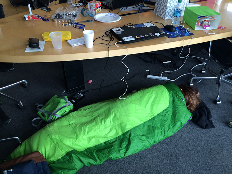 A student sleeps in a green sleeping bag during the Getty Game Jam