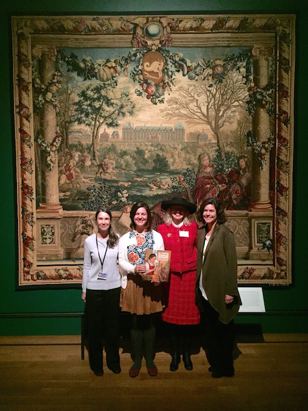 Charissa Bremer-David, Alexandra Hinrichs, Renée Graef, and Elizabeth Nicholson in front of the tapestry Château of Monceaux/Month of December, designed by Charles Le Brun and created at Gobelins, France, before 1712. It is one of two versions hanging in the exhibition Woven Gold: Tapestries of Louis XIV. The design inspired the tapestry Thérèse weaves in Thérèse Makes a Tapestry. Photo by Bruce R. Dean