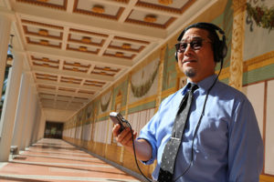 Wearing headphones and holding a recording device, rtist Alan Nakagawa in the Outer Peristyle of the Getty Villa