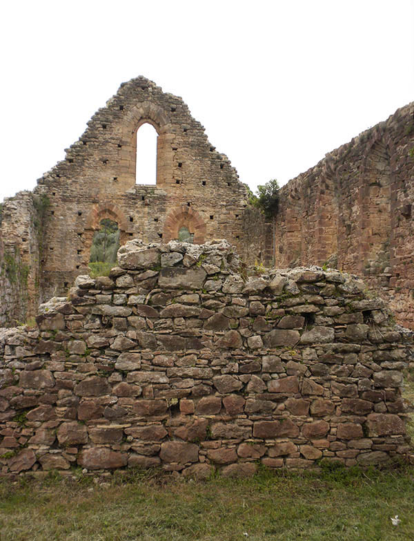 In the foreground is the masonry wall inside the Isova Monastery. The far wall includes pointed-arch window frames.