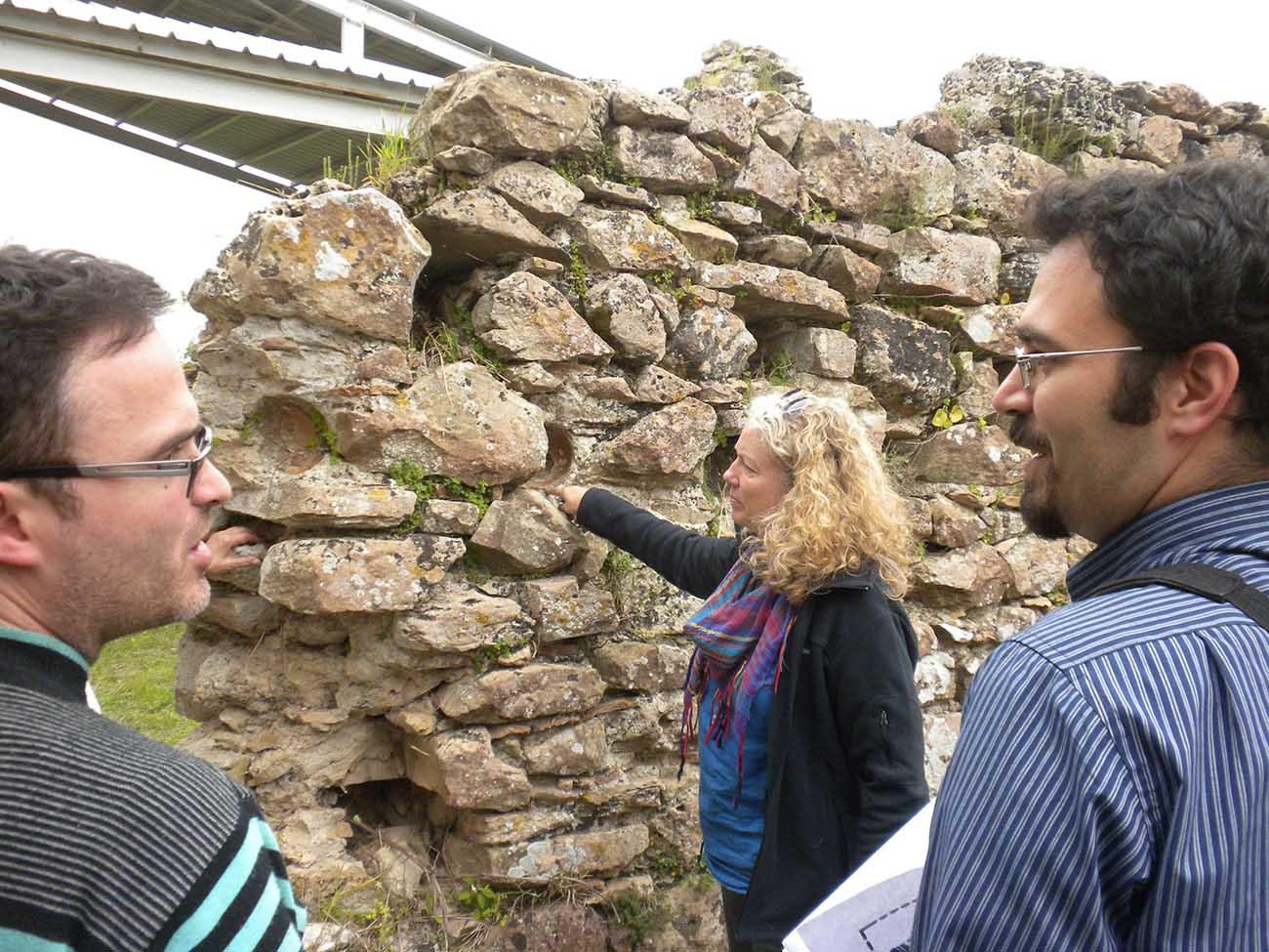 (Left to Right) Gil Fishhof (Tel Aviv University), Edna J. Stern (Israel Antiquities Authority), and Michalis Olympios (University of Cyprus) discuss the construction of the wall in question.