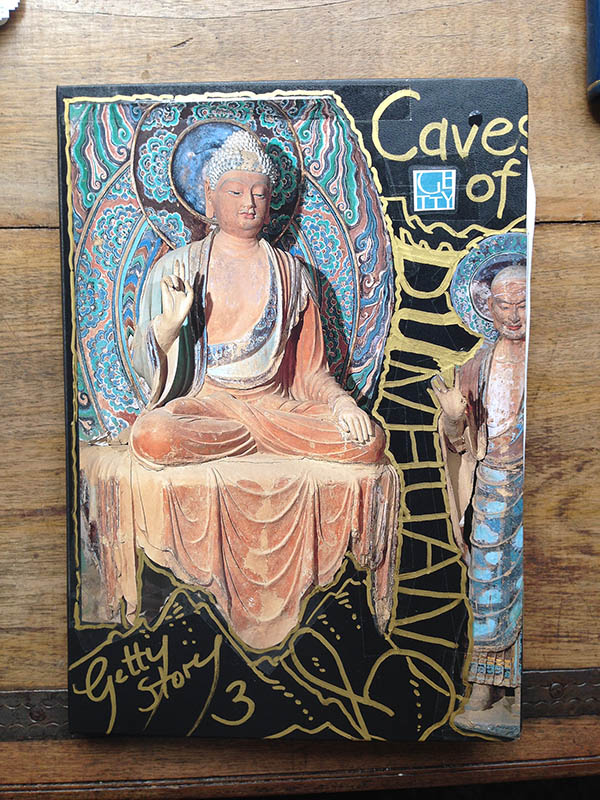 "A colorful drawing of a buddha graces the cover of Cornelia Funke's research notebook for ""Voyage into the Caves of the Thousand Buddhas"""