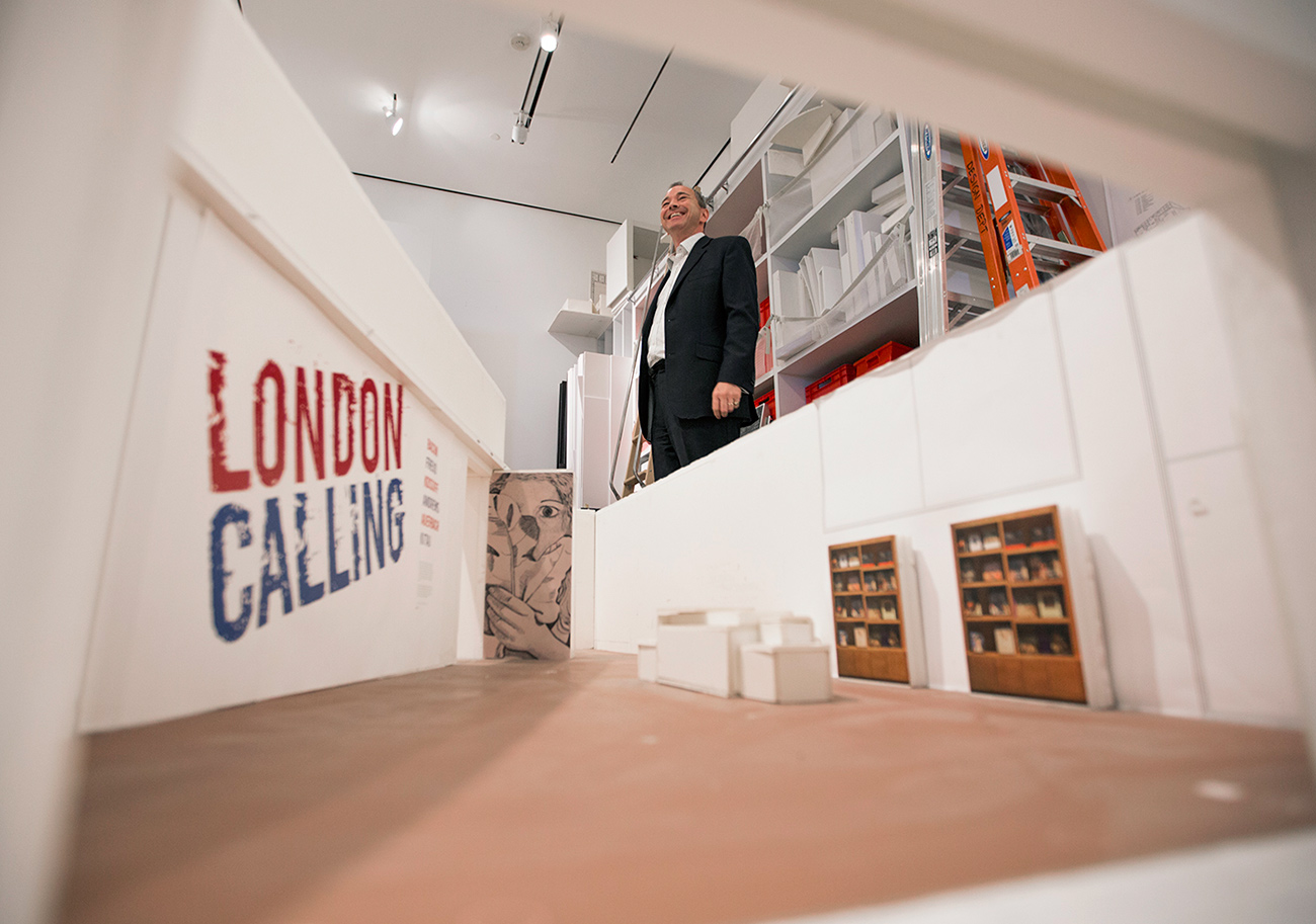 Getty Museum curator Julian Brooks smiles while standing beside a foam-core mockup of London Calling