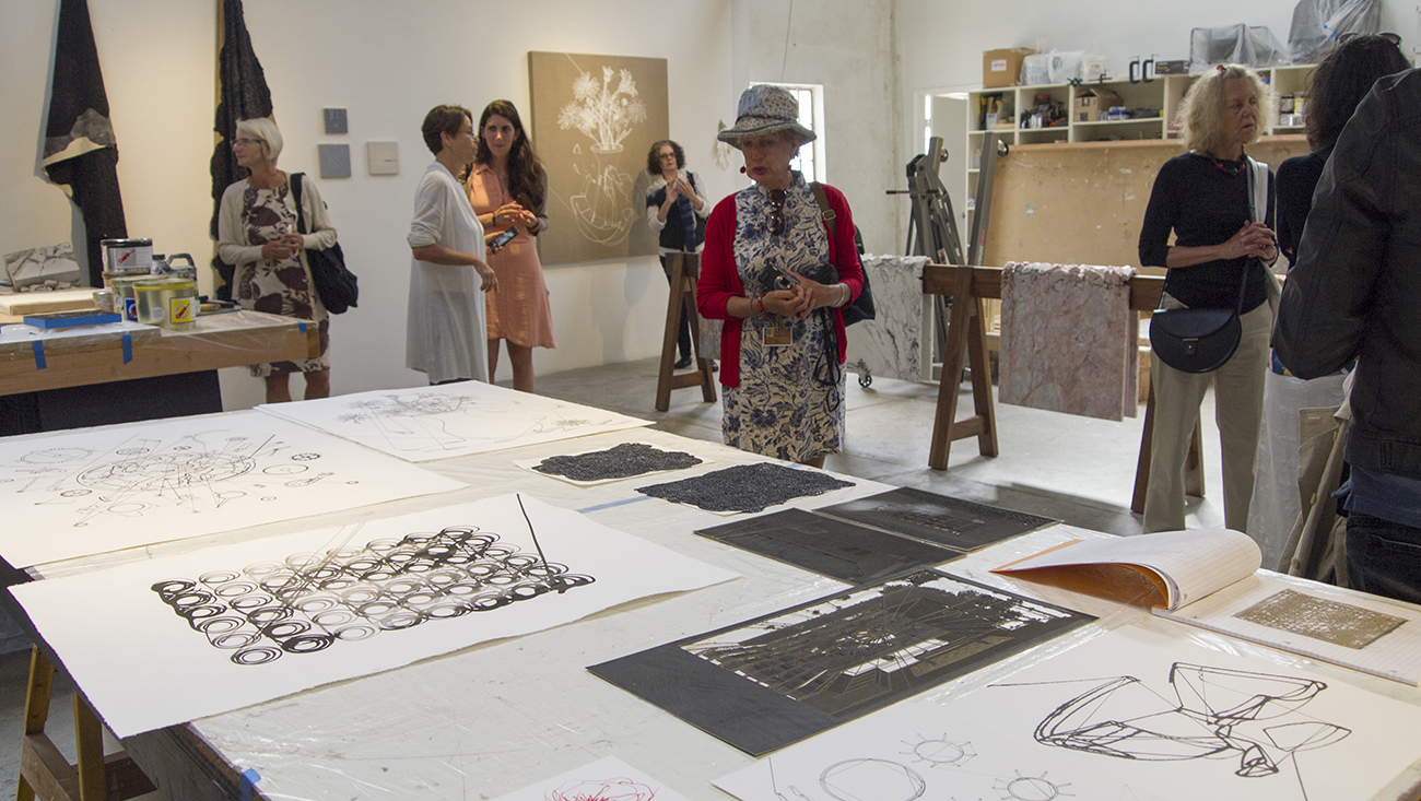 Scholars explore Analia's studio, which is filled with raw materials and artworks at various stages of completion, including her draped marbles (center-right of the image).