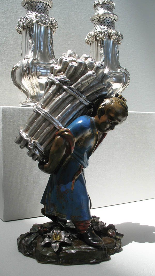 Foreground: painted bronze and silver figure of a boy carrying a bundle of sugarcane; Background: Pair of silver sugar casters
