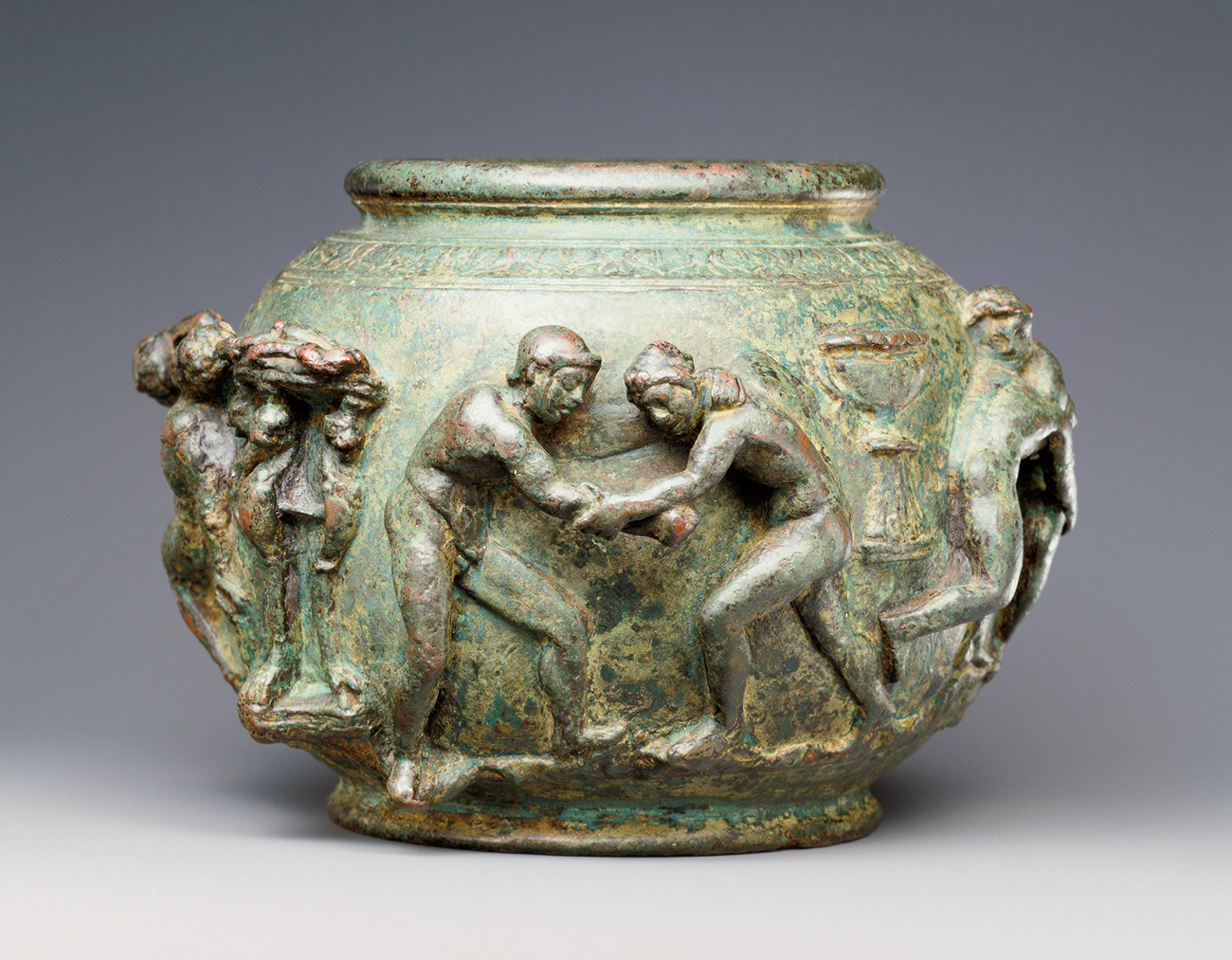 Bronze Roman container showing two naked athletes struggling to gain an advantage over one another during wrestling
