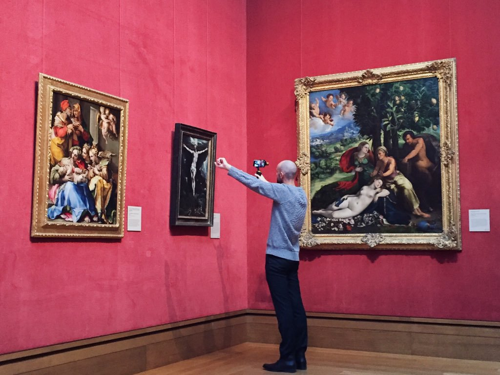 Andrew broadcasting with an iPhone in hand in front of an El Greco painting.