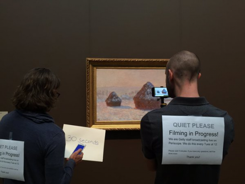 Two Getty staff use an iPhone to broadcast about Monet's Wheatstacks with signs taped to their backs about filming notifications.