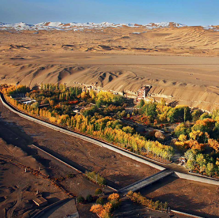 Aerial view of the Mogao Grottoes, looking west, showing desert and snow-capped mountains in the far distance