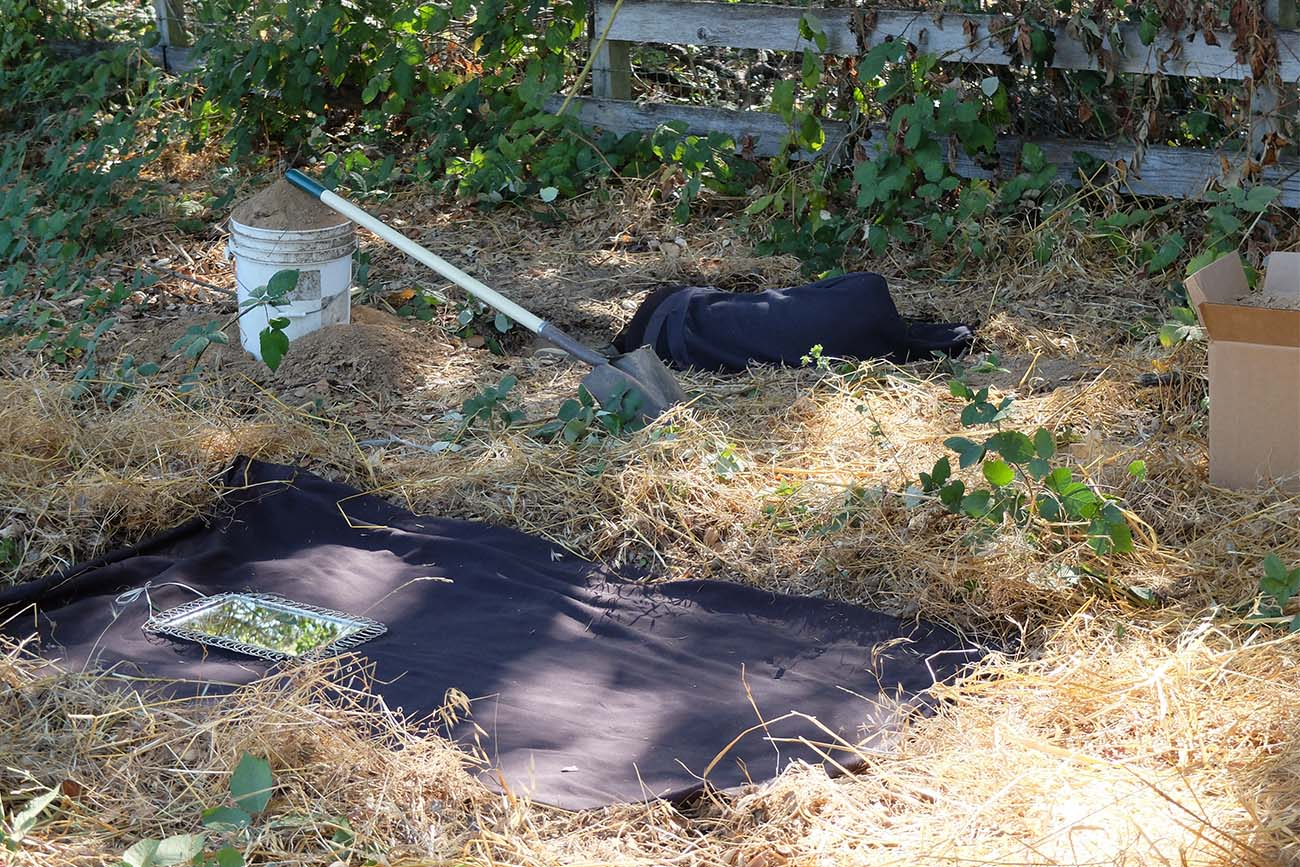 In the foreground, a black cloth covers a cleared rectangle of earth. Marbles Jumbo Radio lies on the ground in the background.