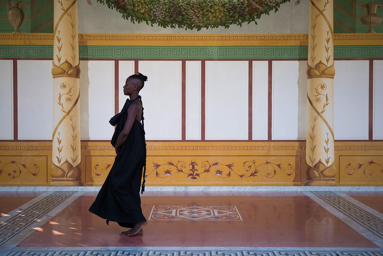 taisha paggett walks in the covered walkway surrounding the Getty Villa's Outer Peristyle Garden.