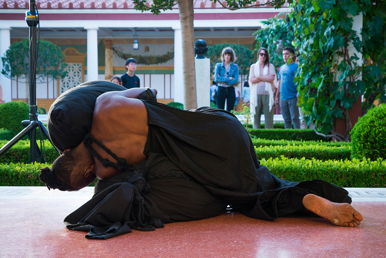 Lying down in the covered walkway of the Getty Villa's Outer Peristyle Garden, taisha paggett embraces the Literal Weight during her performance of Mountain, Fire, Holding Still at the Getty Villa.