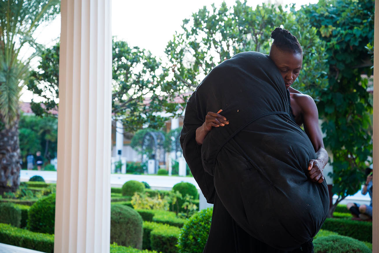taisha paggett carries the Literal Weight during her performance of Mountain, Fire, Holding Still at the Getty Villa.