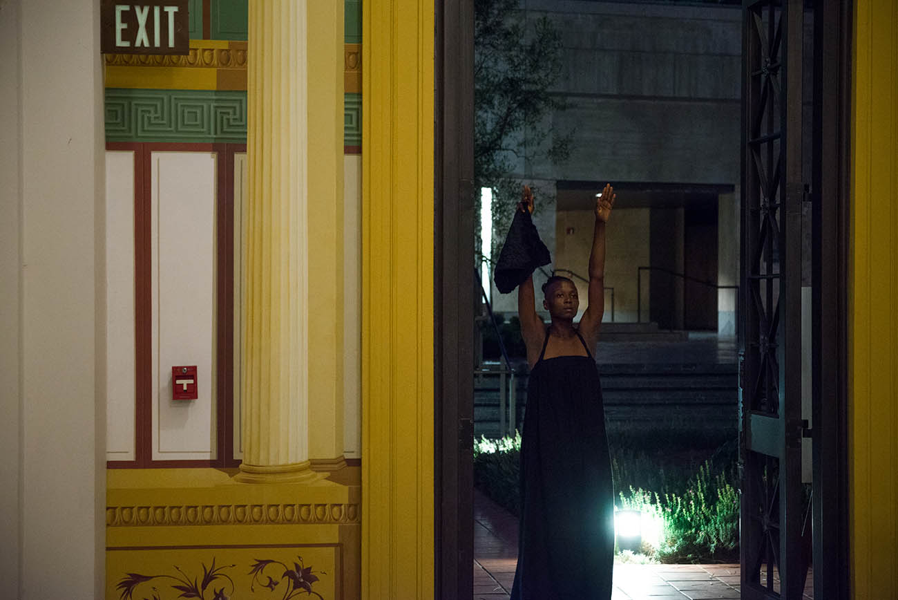 With arms raised, taisha pagget dances in the Getty Villa's Outer Peristyle Garden.