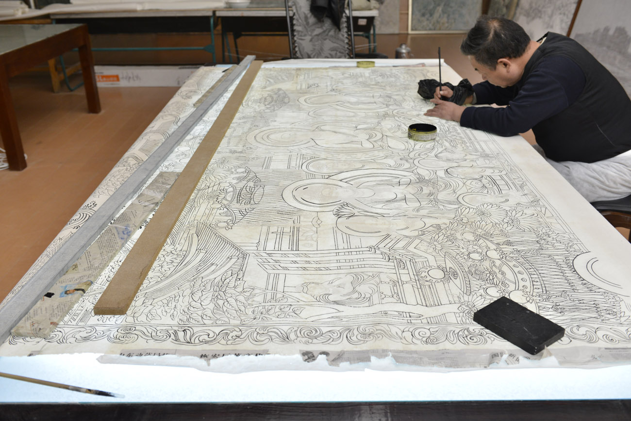 An artist captures the outlines of a wall painting in painstaking detail before the addition of color can begin. Image courtesy of the Dunhuang Academy