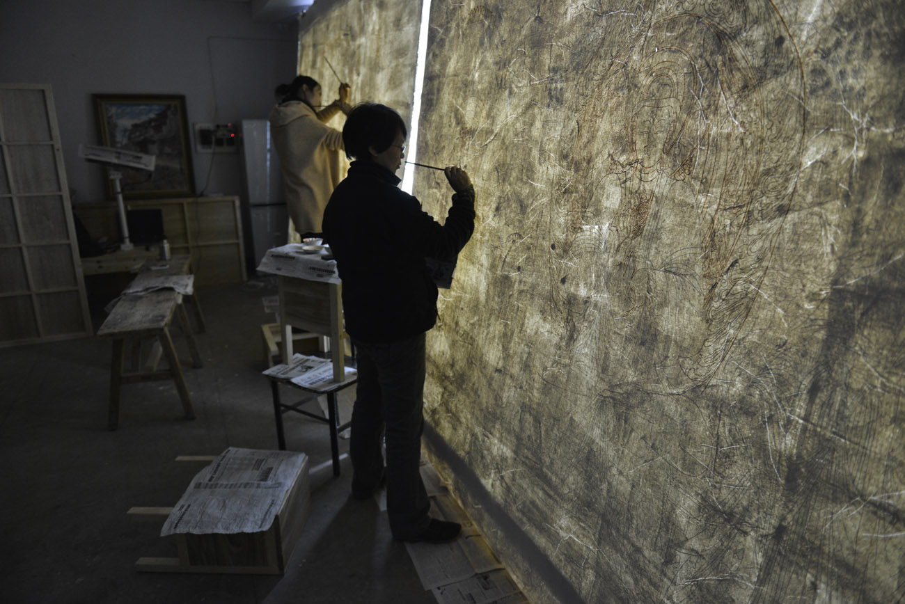 Two artists stand with brushes by a large piece of paper, tracing outlines against a wall of light