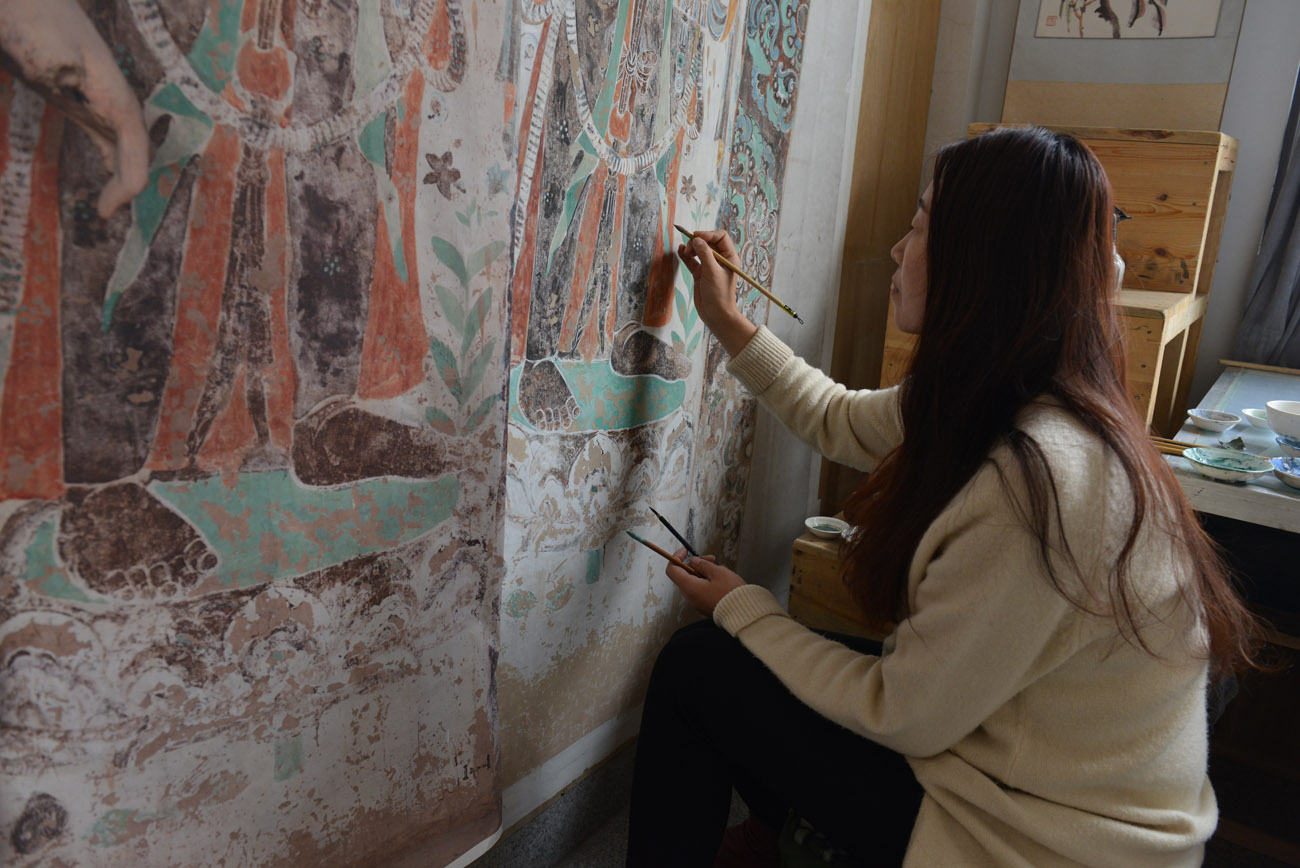 Seen from behind, a Chinese woman artist paints a red and green painting on mulberry paper