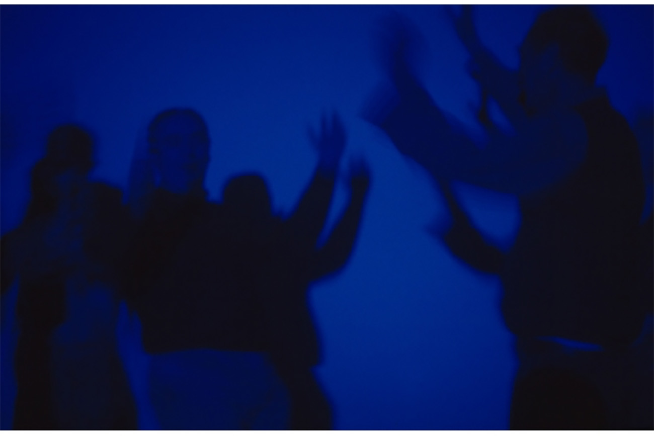 Still from Derek Jarman's Blue with silhouettes of people amidst a screen filled with International Klein Blue.