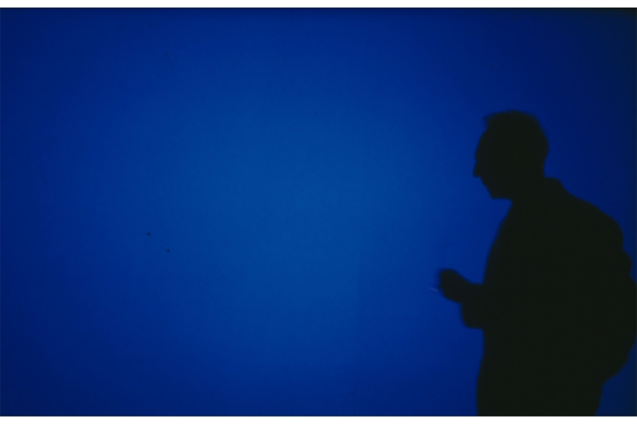 Still from Derek Jarman's Blue with a silhouette of a man amidst a screen filled with International Klein Blue.