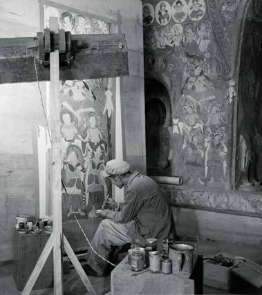 Black and white photograph of an artist in a hat working in detail on a large Chinese wall painting