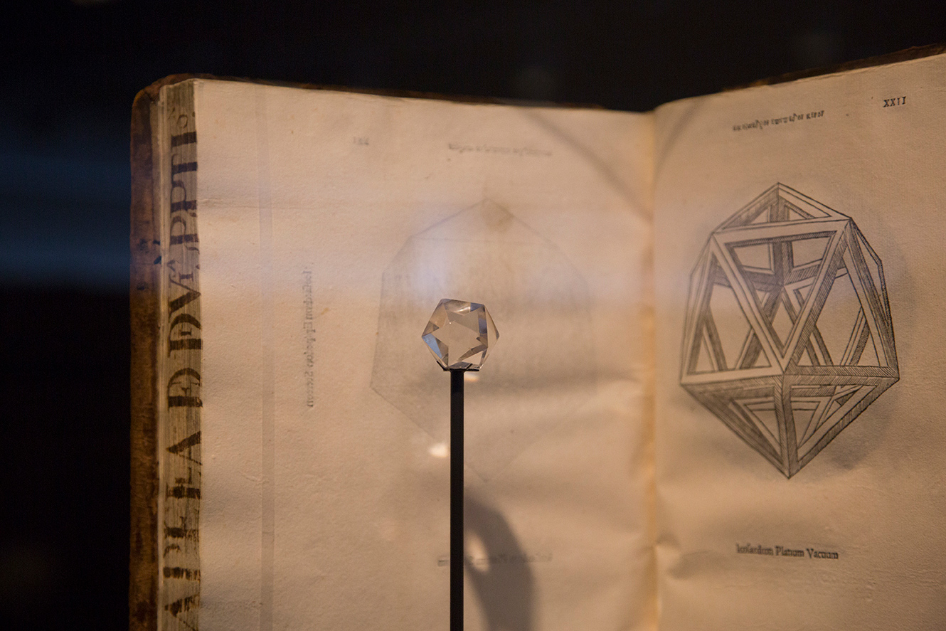 Close-up of an ancient crystal juxtaposed with a Renaissance book showing a schematic of its design