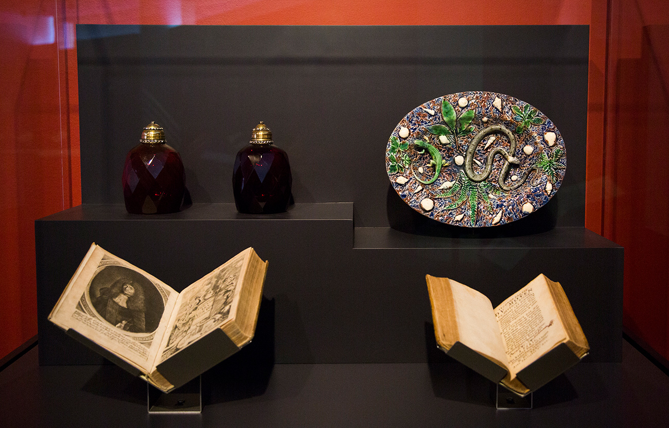 A case with two early books, dark red glass bottles, and a painted oval plate with a lizard and snake in relief