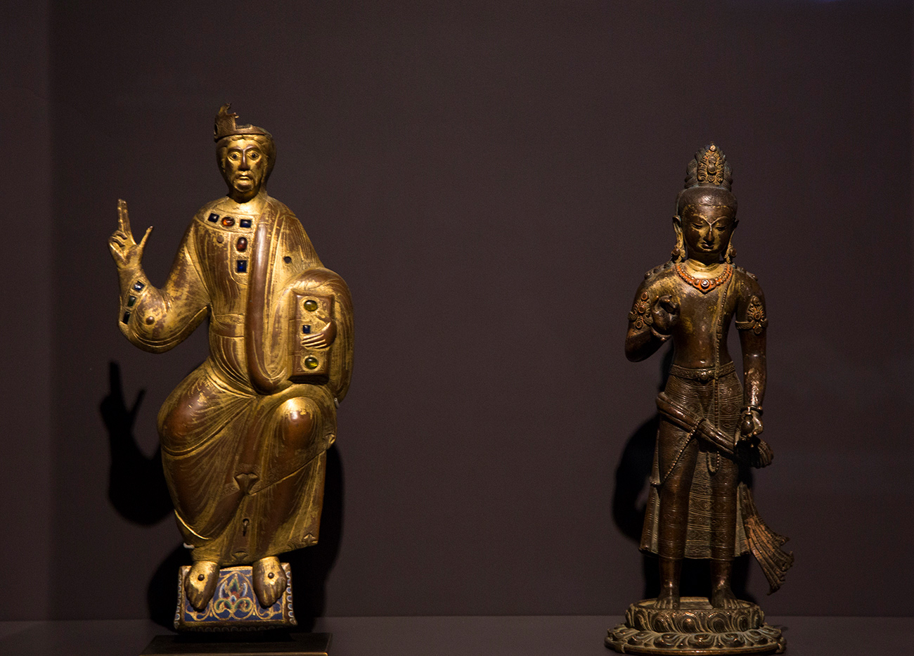 Two small metal devotional sculptures side by side in case, both with their right arms raised in blessing