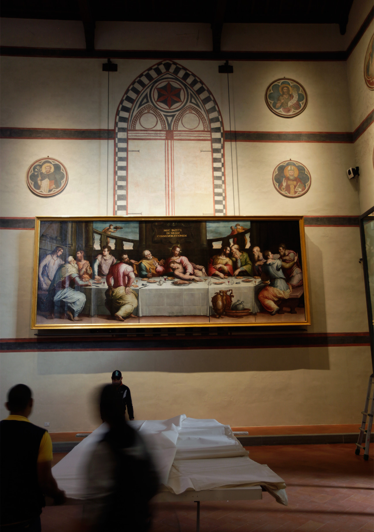 A painting of the las supper hangs high on the wall of a low-lit, churchlike interior