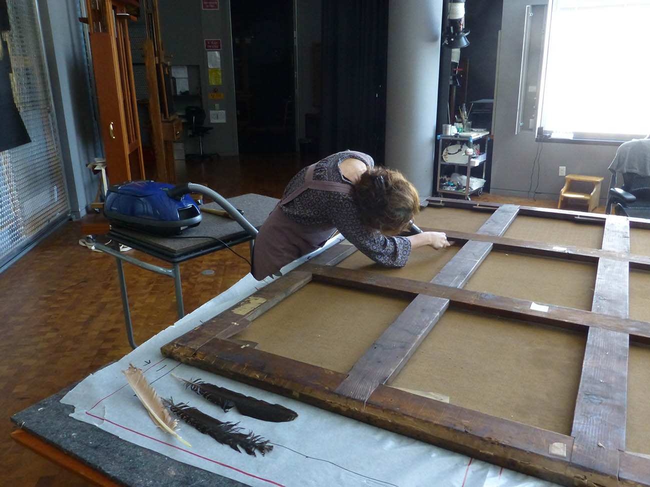 Vacuuming the back of the canvas to remove excess dirt. The goose feathers, seen in the foreground, are what I used to dislodge dust and dirt on the back of the lining canvas and under the wooden stretcher bars.